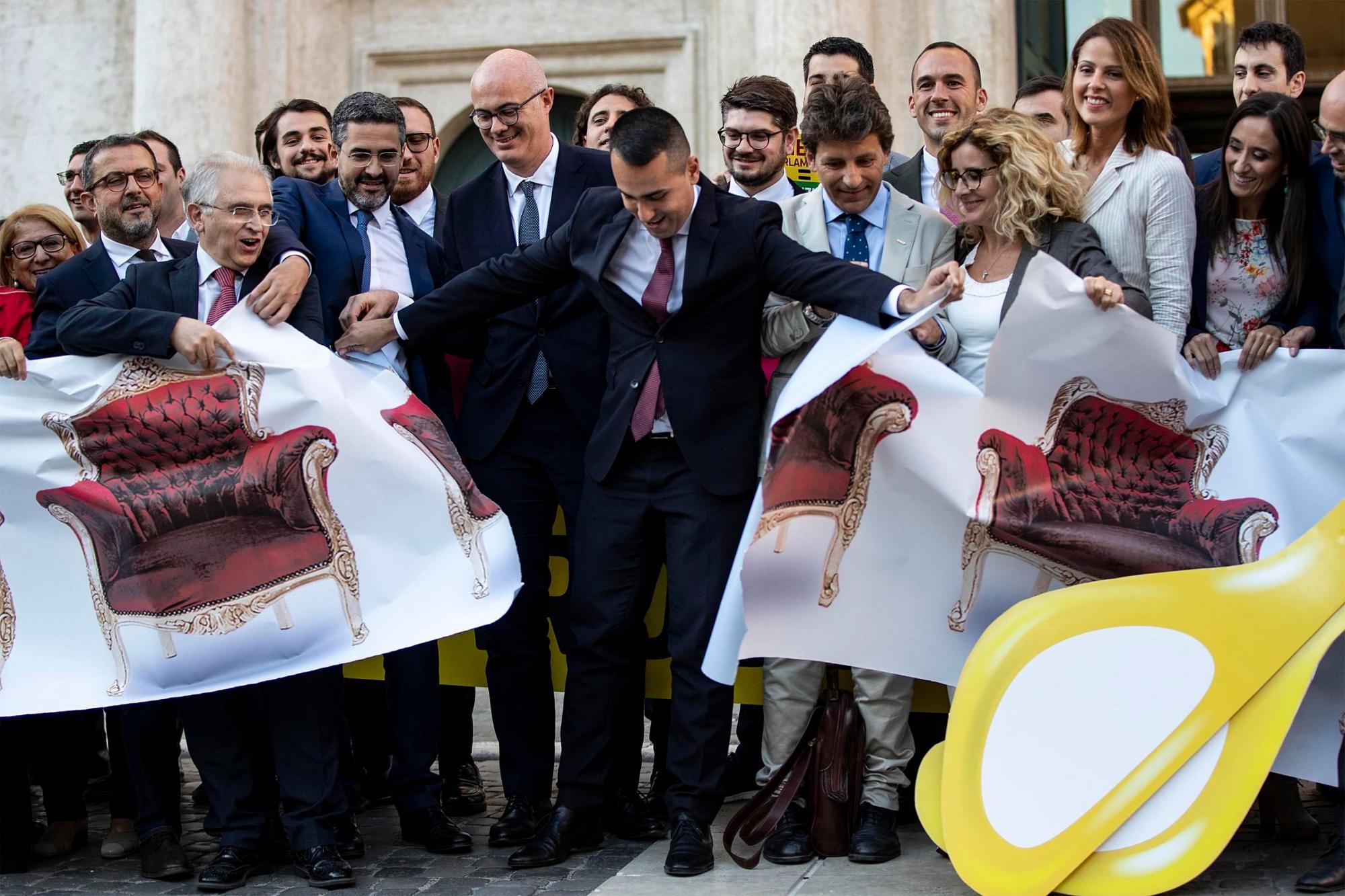 Luigi Di Maio (C), ministro de Exteriores italiano, exhibe unos escaños de papel antes de la votación/Efe