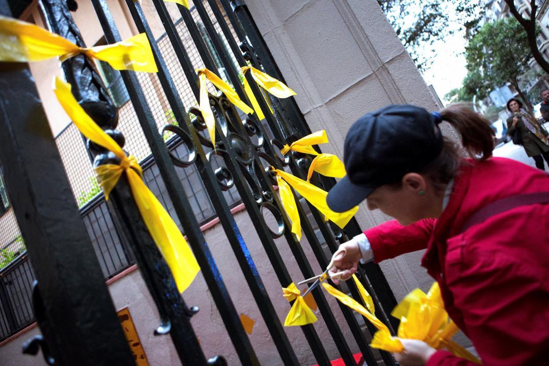 Una joven retira de los Grupos de Defensa y Resistencia (GDR), contrarios a la independencia de Cataluña, retirando lazos amarillos